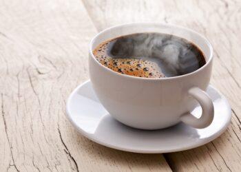 Eine Tasse schwarzer Kaffee auf einem Holztisch