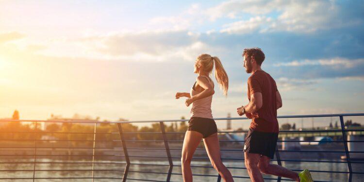 Eine Frau und ein Mann beim Joggen auf einer Brücke
