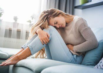 Eine Frau hat Bauchschmerzen und hält sich mit angewinkelten Knien eine Hand auf den Bauch.