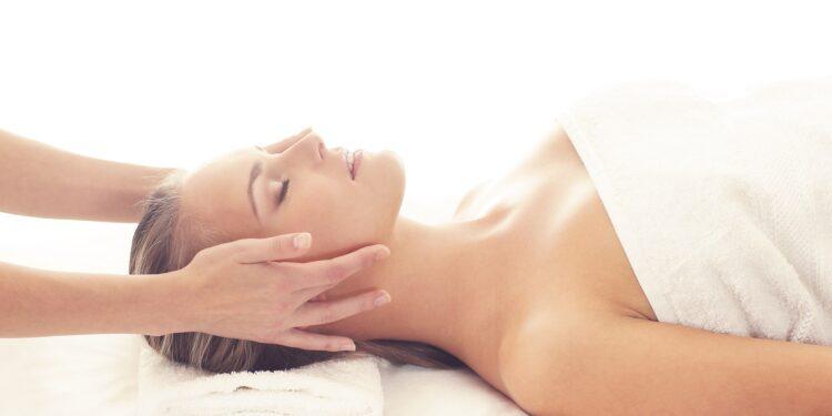 Eine Frau liegt auf dem Rücken und erhält eine Kopfmassage.