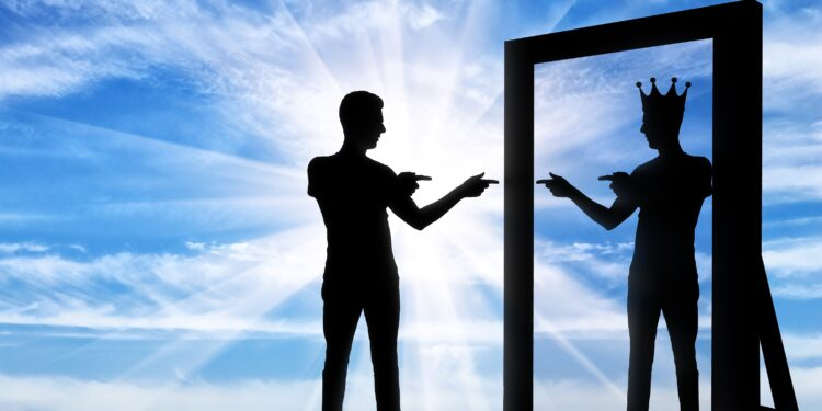 Ein Mann sieht sich selbst als König im Spiegel.