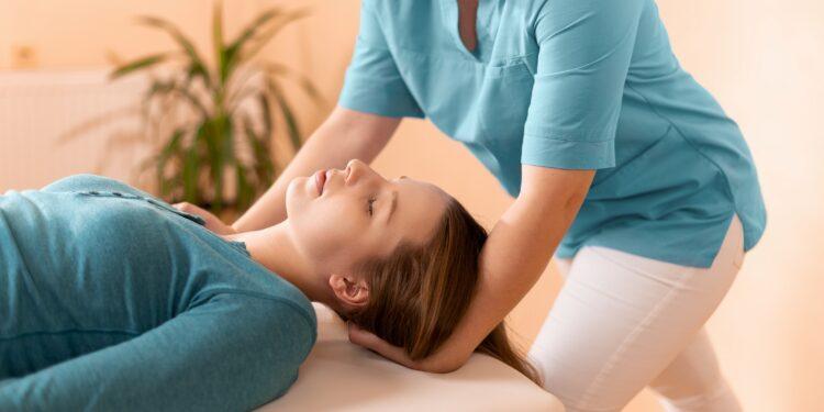 Behandlerin therapiert den Nacken einer Patientin