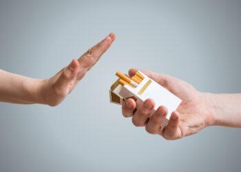 Eine Person reagiert mit einer ablehnenden Geste als ihr Zigaretten angeboten werden.
