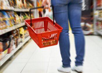 Eien Hand hält einen roten Einkaufskorb im Supermarkt
