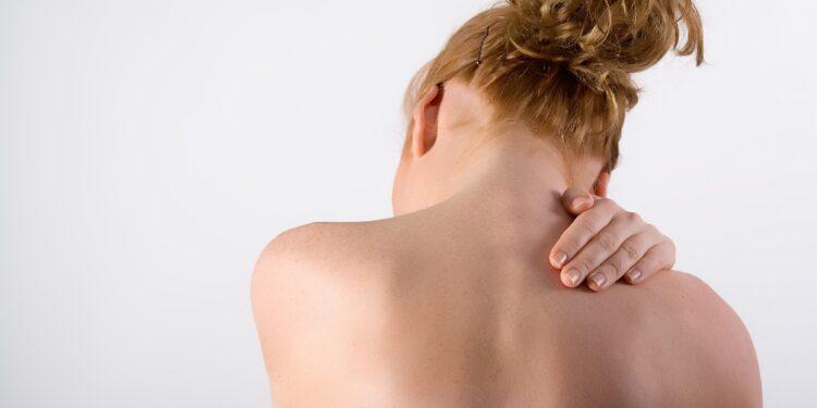 Frau hält sich vor Schmerzen den Rücken.