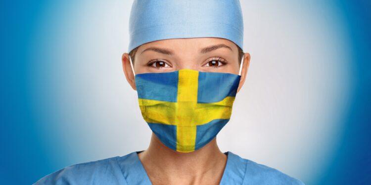 Eine Frau trägt eine Mund-Nasenschutzmaske in den Farben der schwedischen Flagge.