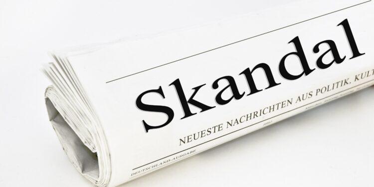 """Auf der Titelseite einer Zeitung steht das Wort """"Skandal""""."""