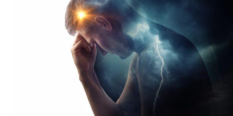 Ein Mann senkt den Kopf und fasst sich an die Stirn.