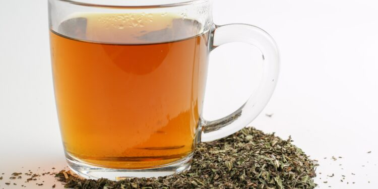 Ein Glas mit Tee steht inmitten getrockneter und zerkleinerter Minzblätter.