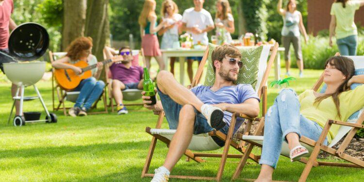 Junge Menschen bei einer Grillveranstaltung auf einer Wiese.