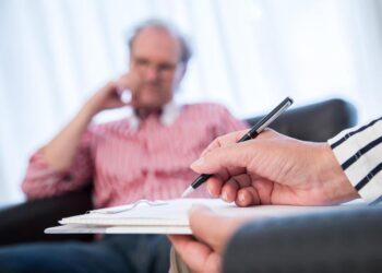 Ein Mann sitzt in einem Sessel während einer psychologischen Sprechstunde.