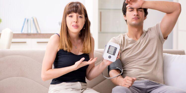 Eine Frau misst bei einem Mann den Blutdruck.