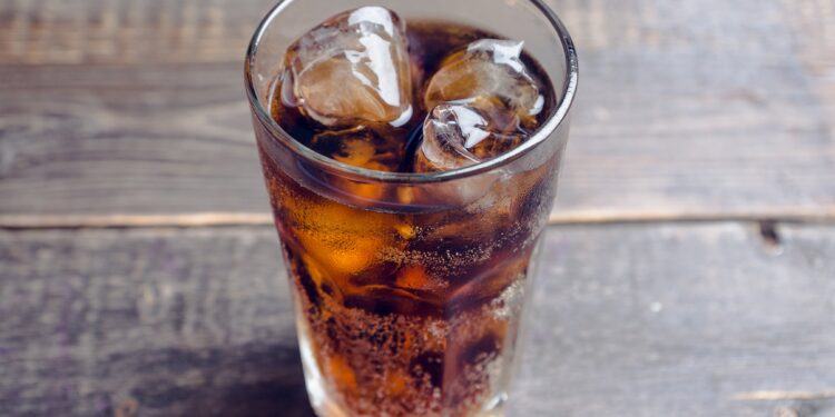 Ein mit Cola und Eiswürfeln gefülltes Glas auf einem Holztisch