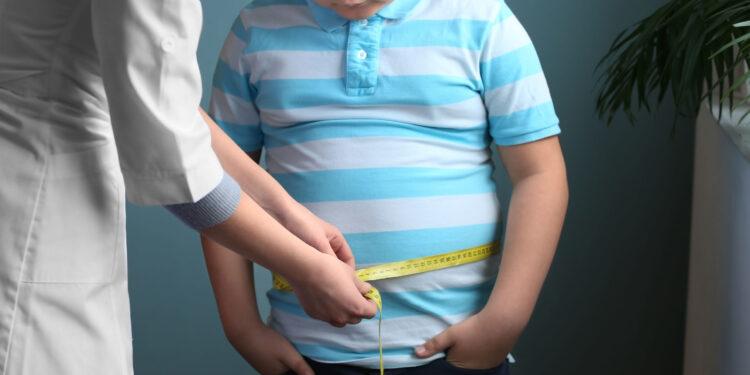 Eine Ärztin misst den Bauchumfang bei einem übergewichtigen Jungen.