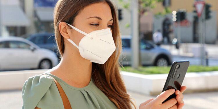 Junge Frau mit Mund-Nasen-Schutz blickt auf ihr Smartphone