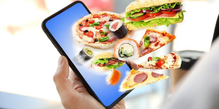Grafische Darstellung eines Smartphones, aus dem ungesunde Lebensmittel wie Pizza und Burger herausfliegen.