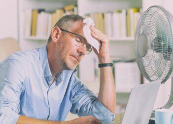 Mann im Homeoffice leidet unter Hitze und versucht, sich durch einen Ventilator abzukühlen
