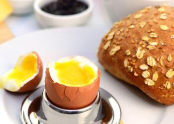 Ein geöffnetes Frühstücksei im Becher neben einem Brötchen und einer Tasse Kaffee