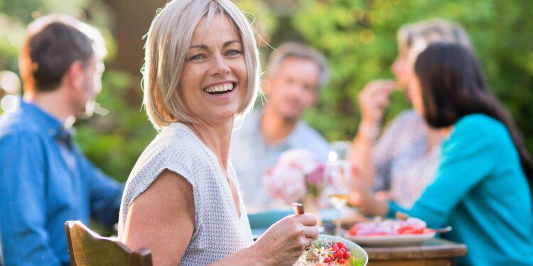 Eine Frau in den Vierzigern mit einer Schüssel gemischten Salats in der Hand sitzt mit Freunden an einem Tisch in einem Garten
