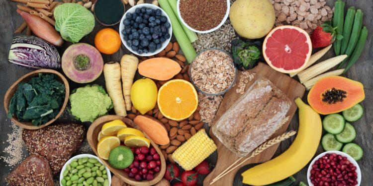 Eine Tischplatte voller pflanzlicher Lebensmittel wie Obst, Gemüse, Hülsenfrüchten und Vollkornprodukten
