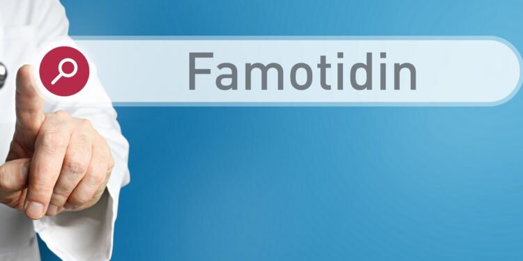 Arzt im Kittel zeigt mit dem Finger auf ein Suchfeld mit dem Wort Famotidin im Fokus