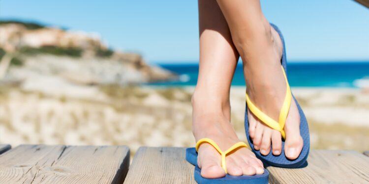 Frauenbeine in Flip-Flops am Strand