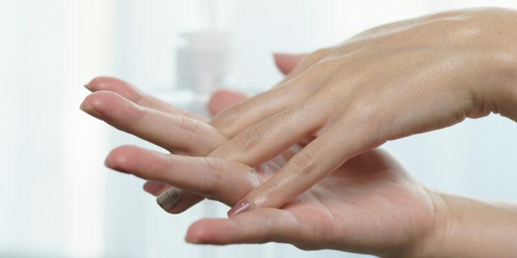 Weibliche Hände verreiben Desinfektionsmittel