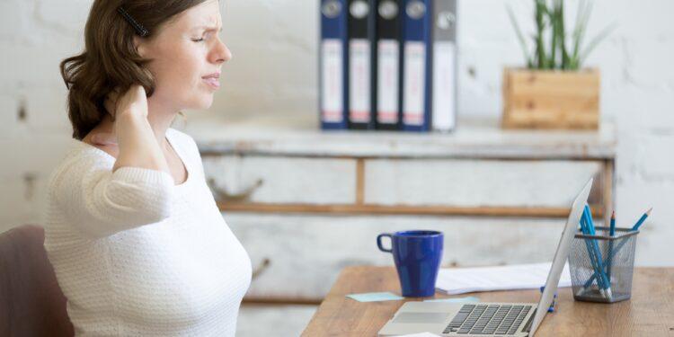 Junge Frau am Büroarbeitsplatz fasst sich an den schmerzenden Nacken