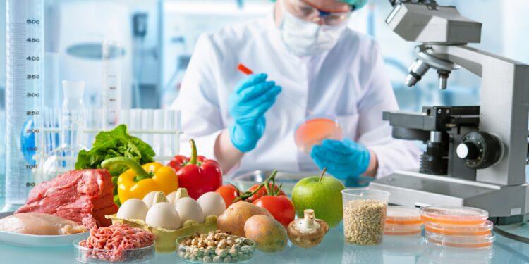 Eine Person mit Schutzausrüstung kontrolliert Lebensmittel.