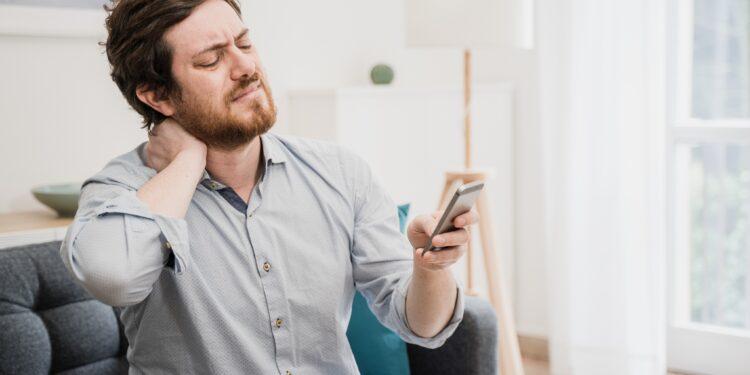 Mann mit schmerzverzerrtem Gesicht fasst sich an den Nacken und blickt auf sein Smartphone