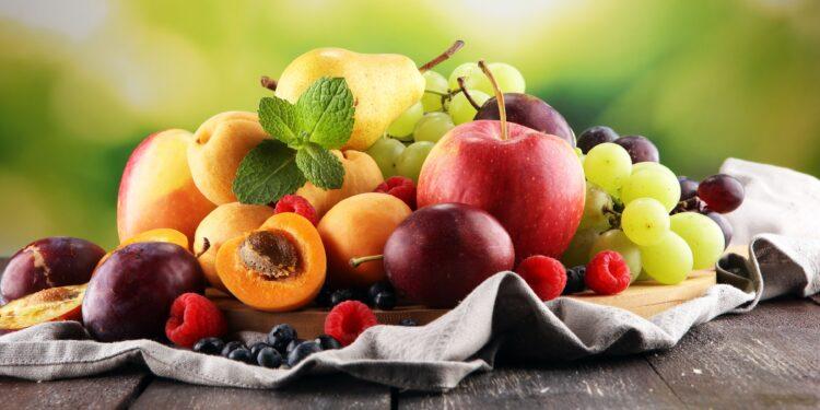 Frische Sommerfrüchte wie Äpfel, Trauben, Beeren, Birnen und Aprikosen auf einem Tisch