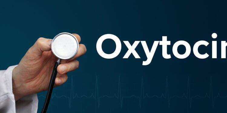 Arzt im weißen Kittel hält ein Stethoskop neben den Schriftzug Oxytocin