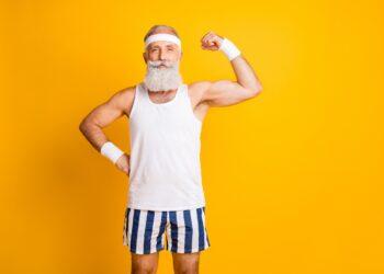 Ein älterer schlanker Mann zeigt seine Oberarmmuskeln.