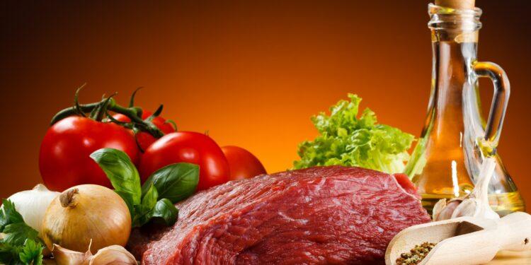 Ein Stück Rindfleisch liegt zwischen gesunden Nahrungsmitteln.