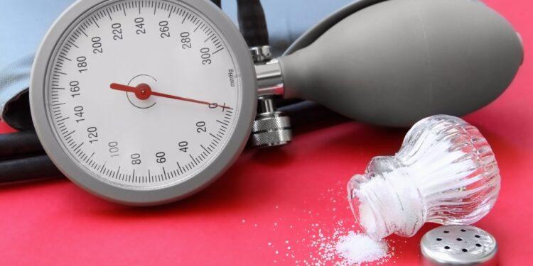 Ein Blutdruckmessgerät und ein umgefallener geöffneter Salzstreuer auf roter Oberfläche