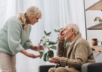 Eine Frau gibt einem älteren Mann ein Glas Wasser und Medikamente