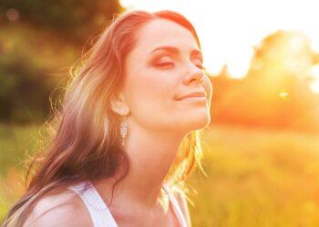 Junge Frau auf der Wiese genießt die Sonnenstrahlen während des Sonnenuntergangs