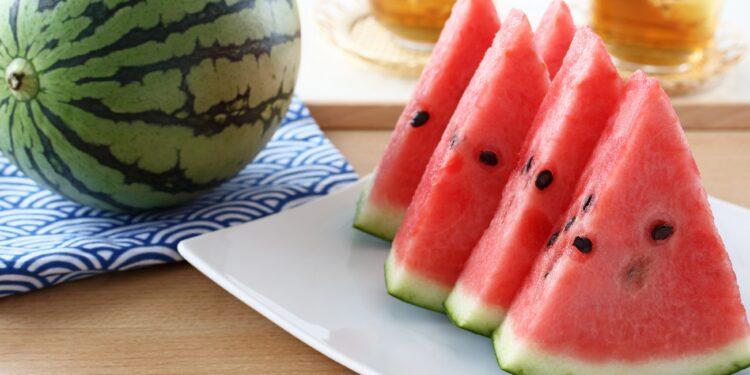 Eine ganze Wassermelone auf einem Tisch neben einem Teller mit geschnittenen Wassermelonenstücken