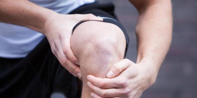Ein Mann umfasst mit beiden Händen sein Knie.