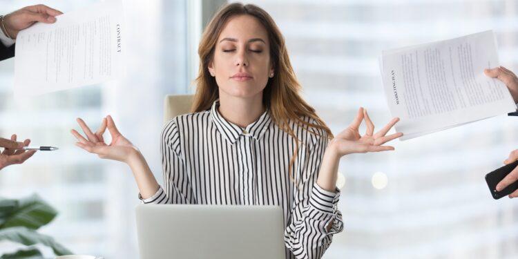 Junge Frau sitzt vor einem Laptop und macht eine Meditationsübung, während von allen Seiten Aufgaben an sie herangetragen werden