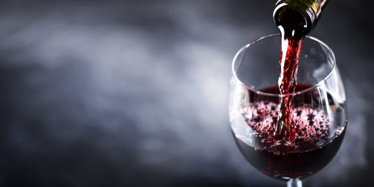 Aus einer Flasche wird Rotwein in ein Glas geschenkt