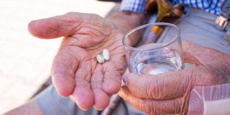 Senior mit zwei Tabletten und einem Glas Wasser in seinen Händen
