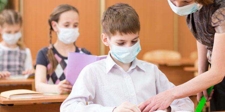 Schulkinder und Lehrerin mit Mund-Nasen-Bedeckungen im Klassenzimmer