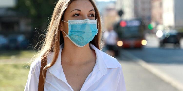 Eine Frau in der Stadt mit Mund-Nasen-Bedeckung