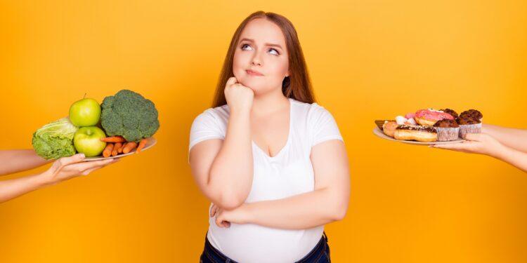 Eine Frau muss sich zwischen gesunden und ungesunden Lebensmitteln entscheiden.