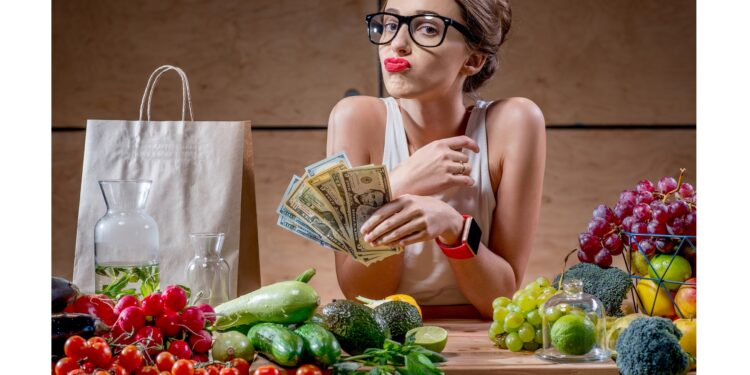Eine Frau hat ein Bündel Geld in der Hand und vor ihr liegen gesunde Lebensmittel.