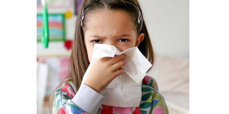 Ein Kind putzt sich die Nase mit einem Taschentuch.