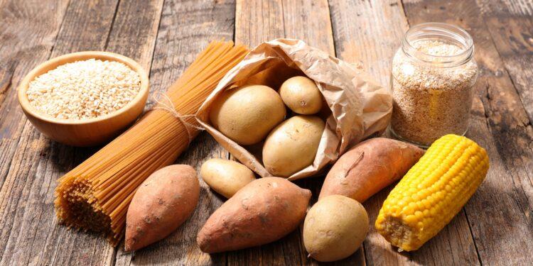 Kohlenhydratreiche Lebensmittel wie Nudeln und Kartoffeln auf einem Holztisch