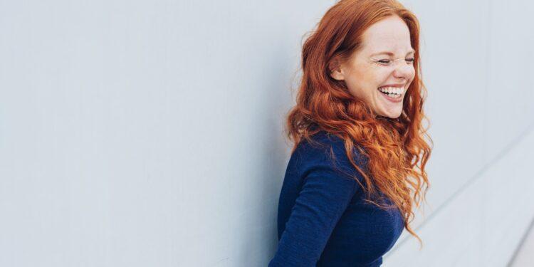 Lachende rothaarige Frau vor einer Wand.