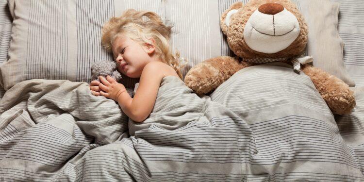 Schlafendes Mädchen mit verzerrtem Gesichtsausdruck im Bett